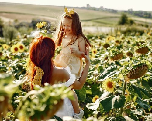 Mother with daughyer in a field. Sunflowers field. Family in a cute clothes