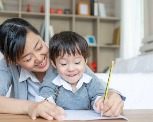 Young mom caught son's hand holding a pencil to  measles write down on white paper, preschool at home, copy space