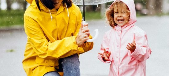Mother with daughter walking in the rain under the umbrella