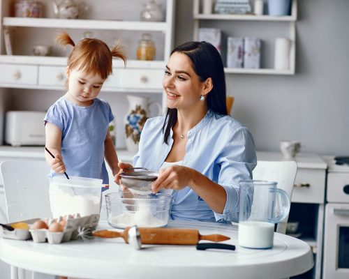Family in a kitchen. Beautiful mother with little daughter. Woman in a blue shirt