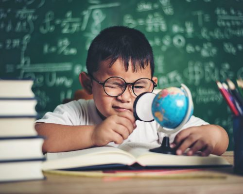 kid observing or studying educational globe model in the classroom.