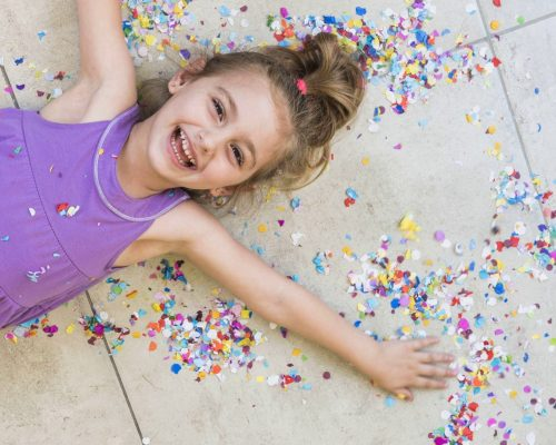 overhead-view-happy-cute-girl-lying-with-confetti-floor_2