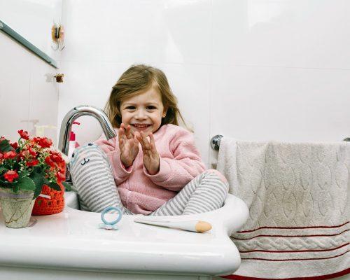 portrait-happy-girl-sitting-bathroom-sink_2