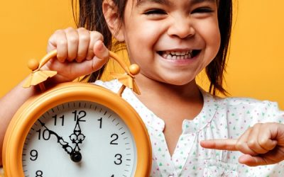 Photo of smiling little girl child standing isolated over yellow background. Looking camera holding clock alarm.